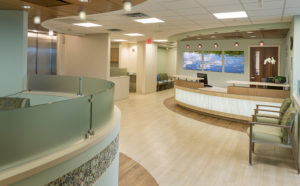 Clean and bright hospital reception area with wood floors, chairs and curved receptionists desk