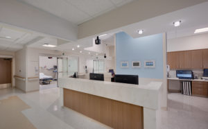 Hospital emergency room station in large, white corridor and blue wall next to patient rooms