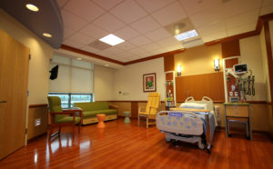Brightly lit patient room with hospital bed couch and glossy wood floors