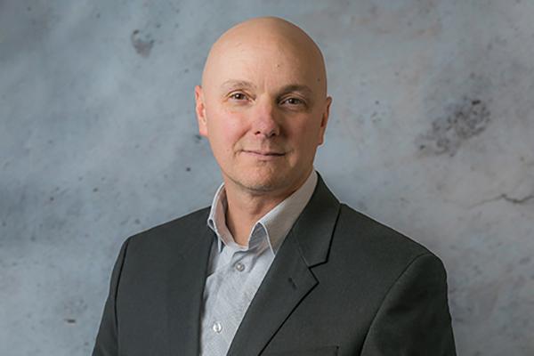 Man smiles while wearing a grey button-down shirt and black blazer - Thomas Morris