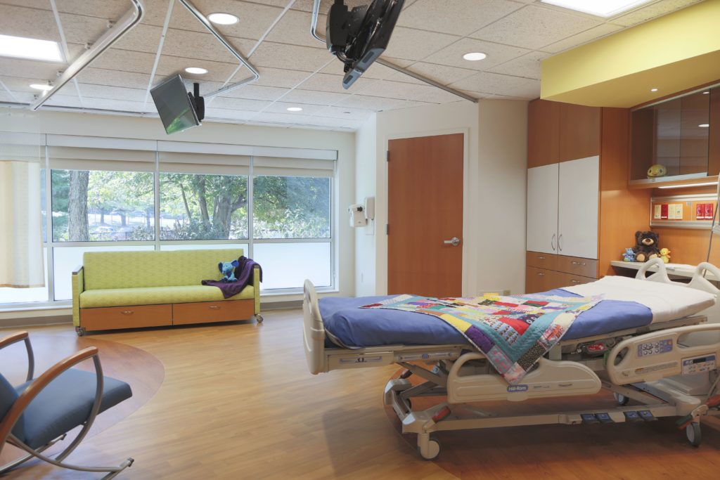 Hospital patient room with chair, couch and bed with colorful blanket
