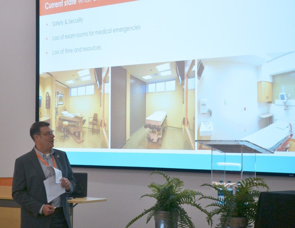 Jon Boyd wears business attire and presents at a conference while looking at large video screen
