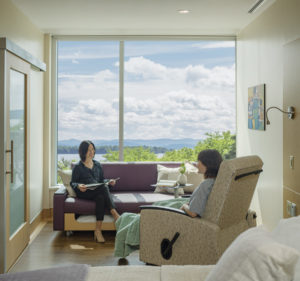 Hospital patient room with two women seated on chair and couch talking
