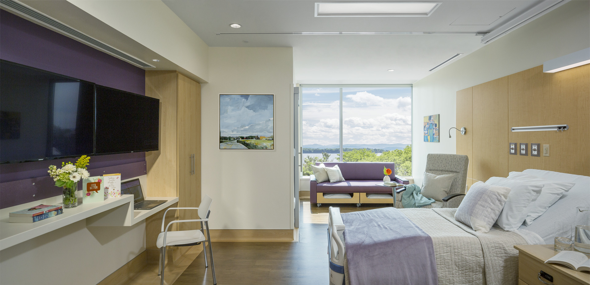 Patient room wth television, desk, laptop, chairs, couches, books, flowers and a bed, with paintings on the walls