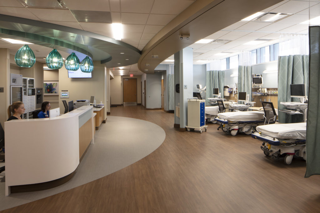 Check-in area of a medical center and three exam tables, chairs, monitors and sets of equipment