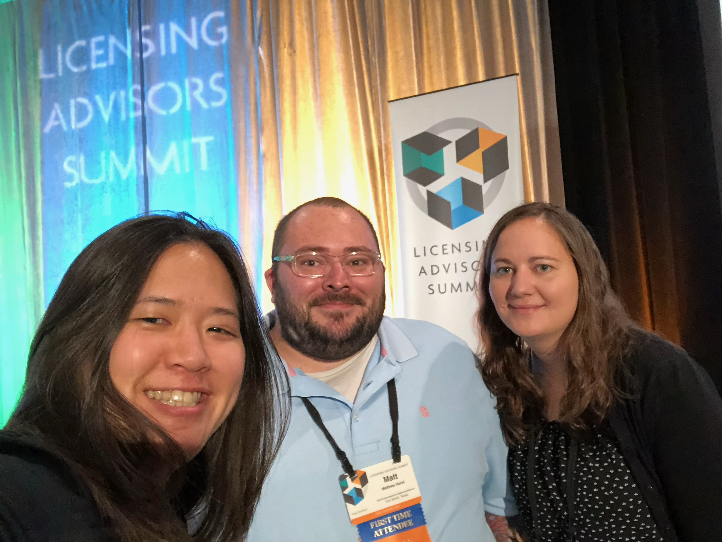 Three people smiling with stage curtain in background at the Licensing Advisors Summit in Minnesota.