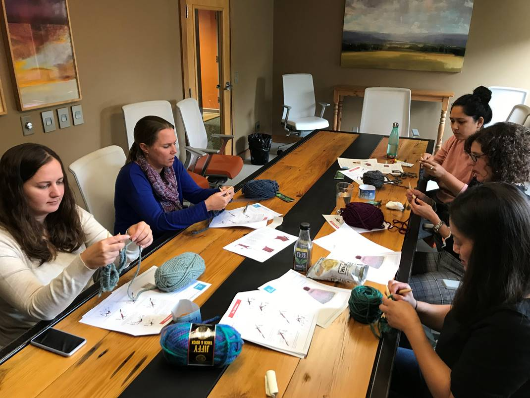 Group of E4H Vermont team members sitting at table knit hats out of colorful yarn for those in need