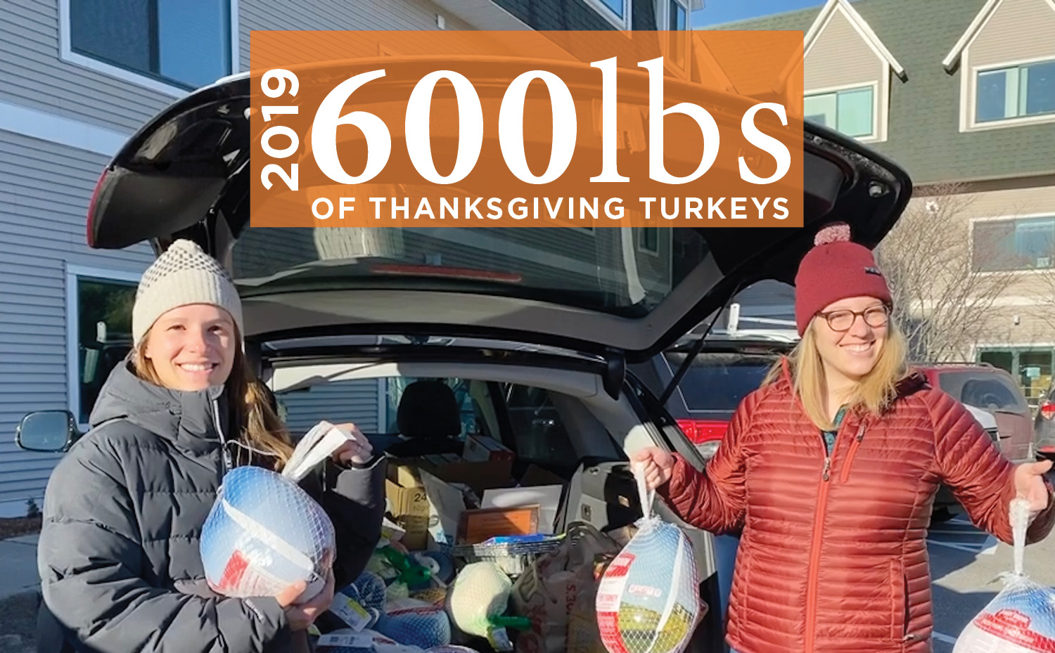 Two smiling women from the E4H Vermont team loading a car and holding turkeys to donate to the local food bank