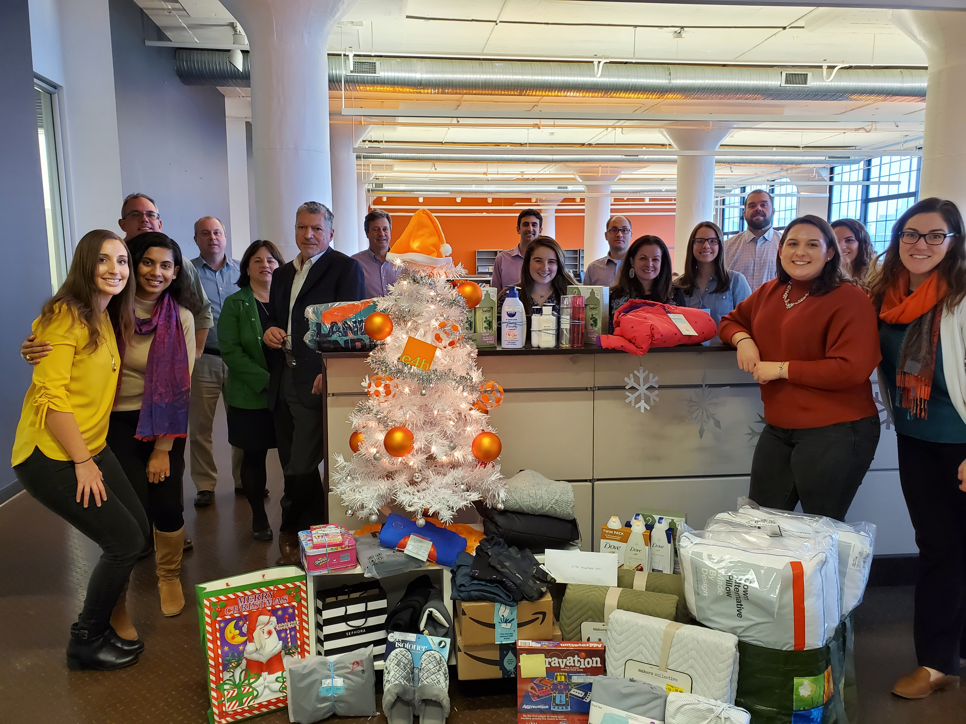 E4H Architecture's Boston team with their decorated holiday tree and wrapped charitable donations underneath