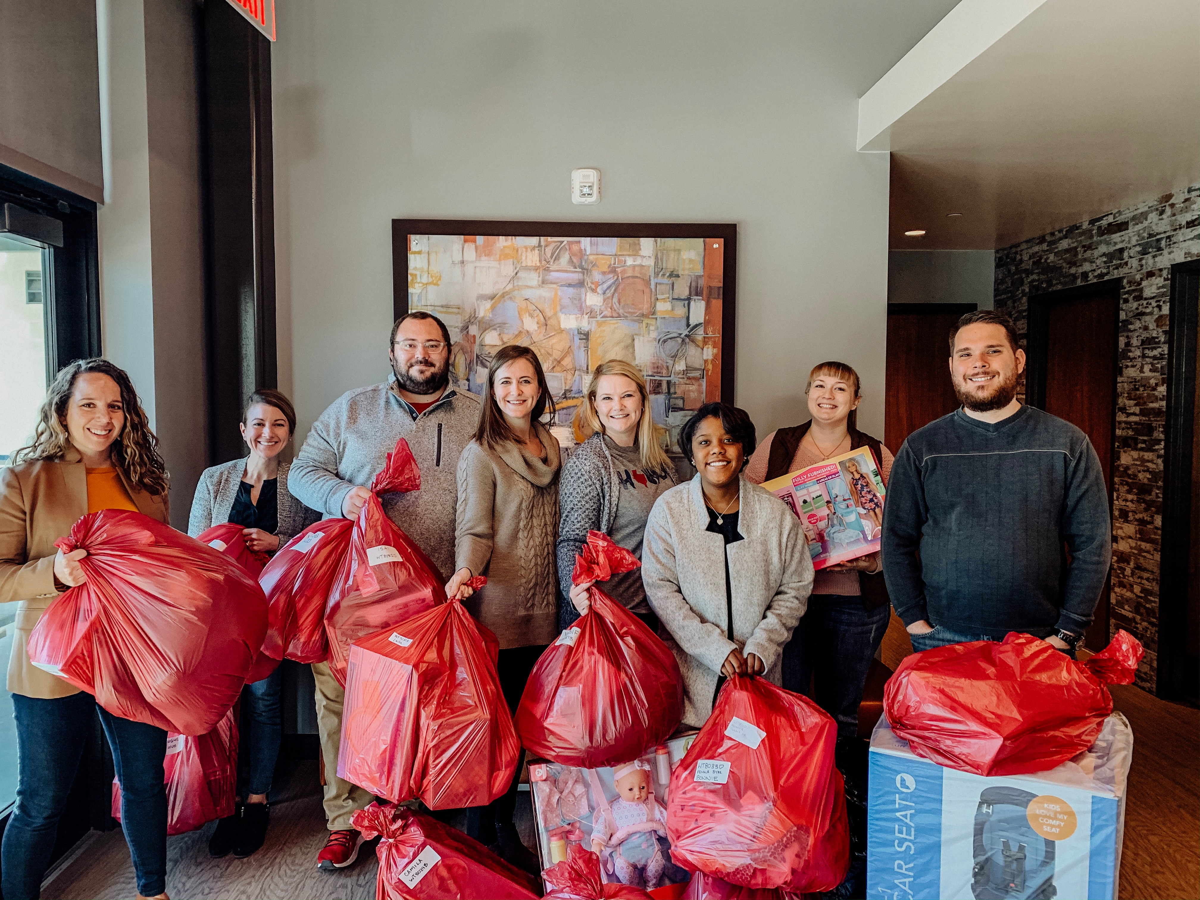 The E4H Fort Worth team with red gift bags for the E4HCares 2019 Donation to Salvation Army