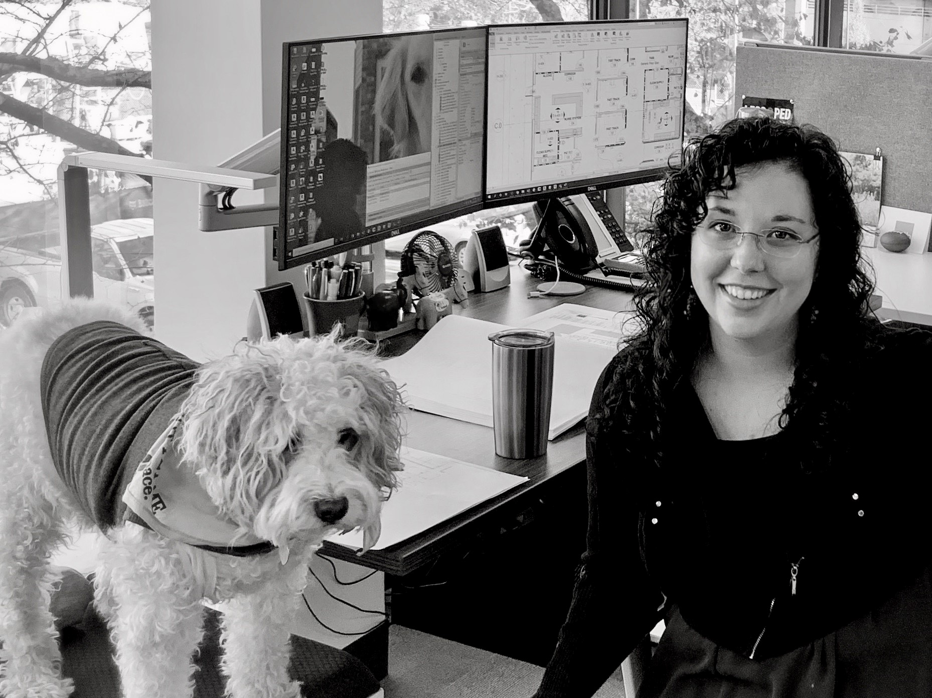 Katie Fligg, Healthcare Designer at her desk with her dog in Nashville